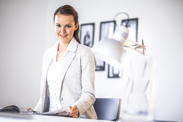 Portrait of confident young businesswoman analyzing brochure at desk in office