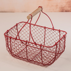 Red wire basket on white background