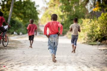 Obraz Kids running on beach sand. Children running to play in Stone Town, Zanzibar Island, Tanzania. Zanzibar daily life. - fototapety do salonu