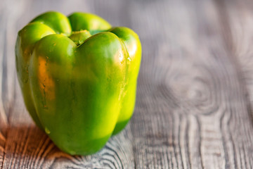 Large green bell paprika pepper on cutting board