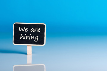 little wooden tag with message We're Hiring. Job offer open new way and give new opportunities
