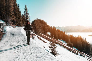 Fotomurales - Woman hiking along snowy trail in mountains