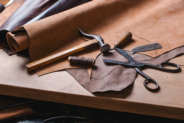 Cobbler tools in workshop on the wooden table . Top view.