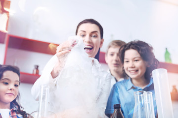 Yay we did it. Female teacher wearing a laboratory coat mixing chemical liquids in a vacuum flask while her emotional pupils standing next to her watching the results of a chemical reaction.