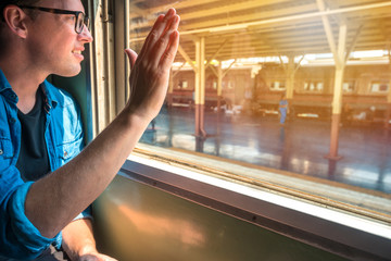 Man sitting in a train raise his hand to say hello or goodbye