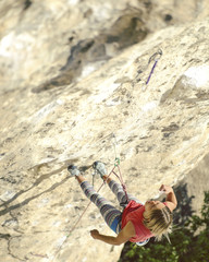 Woman rock climber. Rock climber climbs on a rocky wall. Woman makes hard move.