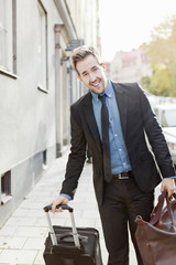 Man in suit holding suitcase