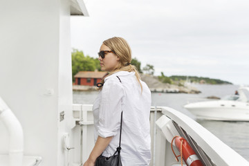 Side view of blonde woman on yacht
