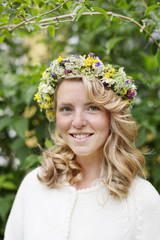 Portrait of young blonde smiling woman with flower wreath on head