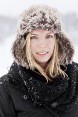 Portrait of smiling young woman in winter coat and fur hat