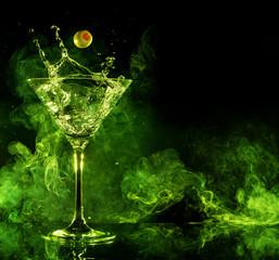 martini cocktail splashing and green smoke in black background