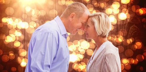 Composite image of happy mature couple facing each other