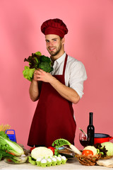 Man in cook uniform offers salad. Chef with smiling face