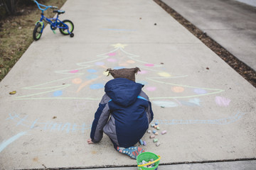 Rear view of boy drawing Christmas tree with chalk on footpath