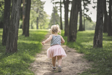 Rear view of girl running on footpath amidst trees at park