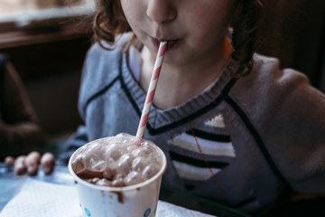 Girl blowing bubbles in chocolate milk