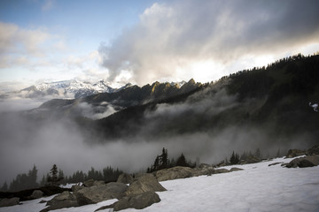 Snow covered field at North Cascades National Park against cloudy sky