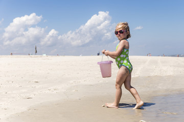 Girl carrying bucket on beach