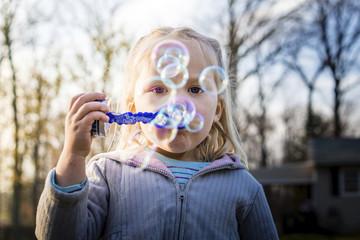 Portrait of girl blowing soap bubbles