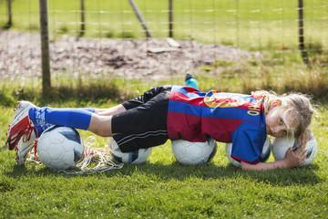 Young girl wearing sportswear lying on balls