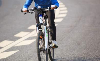 Young Woman Cyclist Riding Mountain Bike on city road.