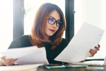 Asian stylish glasses woman designer wear black dress and red lips working with her laptop and checking the document in selective focus..