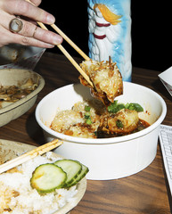 Close-up of woman holding food with chopsticks in restaurant