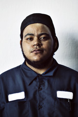 Portrait of young worker wearing uniform against white background
