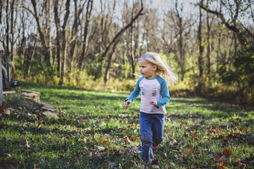 Girl running on grassy field at park during autumn