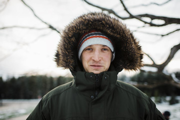 Portrait of man in warm clothing standing against sky during winter