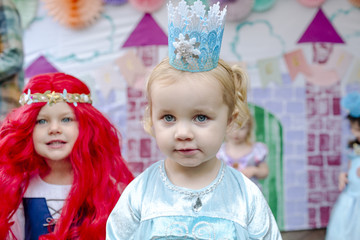 Cute girls against castle painting during princess party