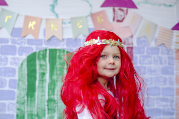 Portrait of smiling girl wearing wig while standing against castle painting during princess party