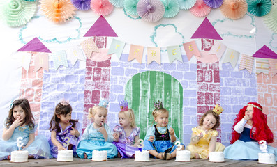 Cute girls having cakes while sitting against castle painting during princess party