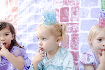 Close-up of girls with fingers in mouth sitting against castle painting during princess party