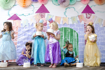 Girls having cakes against castle painting during princess party