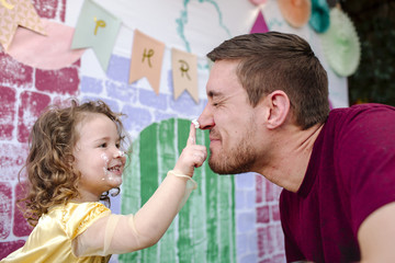 Smiling girl applying cream on father's nose against painted wall