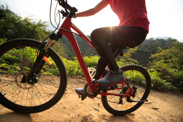 Riding mountain bike on forest trial during sunrise
