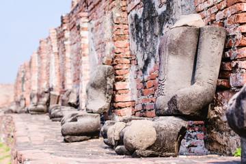 Series of sitting stone Buddha sculptures along a brick wall in Wat Maha Tat, Ayutthaya, Thailand.