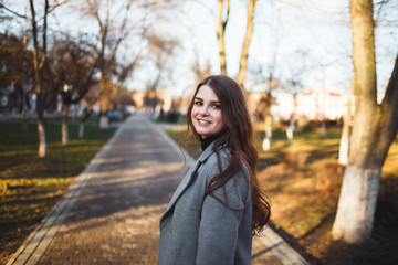 Happy young adult woman walking at beautiful autumn city street