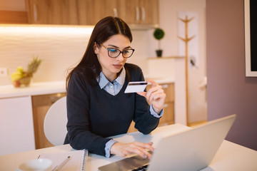 Beautiful girl holding credit card and using laptop. Online shopping concept.