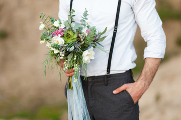 Young groom holding a wedding bouquet, close-up