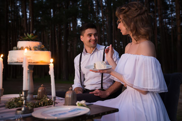 Newlyweds have fun having a wedding cake with candles in the evening in the nature