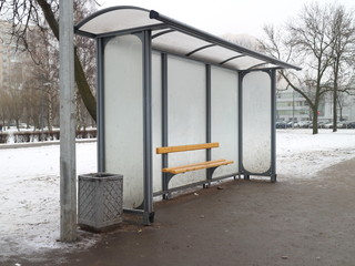 stop of a city bus with a bench on a winter day