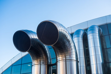 Funnel ventilation ducts on a modern building,  blue sky