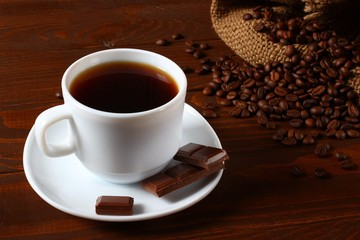 A white pitcher, coffee beans, chocolate and a coffee bag with a wooden background