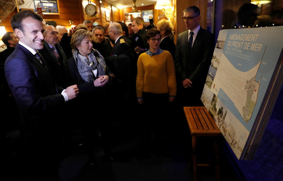 French President Emmanuel Macron looks at a map detailing renovation plans for Calais' sea-front in a restaurant in Calais