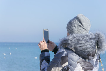 .The girl takes a picture of the sea on the phone..A girl in the winter takes pictures on the phone the sea.Winter landscape of the sea
