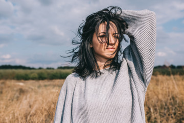 Brunette Caucasian young woman with windy blowing hair outside, against meadow and sky. Portrait of dream female looking away with hand on head. Lifestyle fashion concept. Cover idea mood.