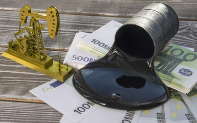 Concept of gold oil drilling a pump, spilled oil from a barrel on a euro banknote money. Business idea