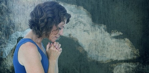 Composite image of upset woman with hands clasped